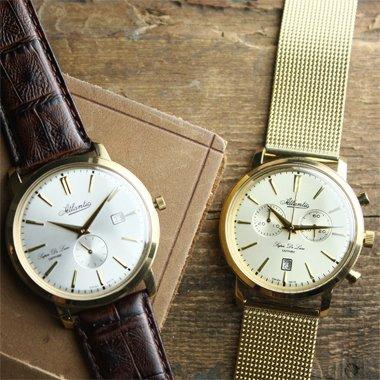 Elegancki, męski zegarek Atlantic 64352.45.21 Super De Luxe na skórzanym brązowym pasku z stalowa koperta w złotym kolorze, pokrytą PVD. Tarcza zegarka jest w białym kolorze z jedną subtarczą oraz datownikiem. Indeksy jak i wskazówki są w złotym kolorze. Drugi zegarek to piekny, męski zegarek marki Atlantic 64456.45.31 Super De Luxe na stalowej bransolecie typu mesh w złotym kolorze. Koperta zegarka Atlantic jest okrągła ze stali w złotym kolorze. Tarcza zegarka Atlantic jest w złotym kolorze ta samo jak wskazówki oraz indeksy.