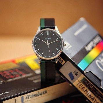 Elegancki, męski zegarek Casio MTP-E133L-1EEF Perfect Duo Coal & Forest na skórzanym pasku w kolorze czarnym i zielonym z srebrną, stalową kopertą. Analogowa tarcza zegarka Casio jest w czarnym kolorze z białymi indeksami w postaci kreseczek.