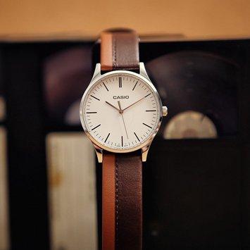 Retro, męski zegarek Casio MTP-E133L-5EEF Perfect Duo Earth & Sunset na skórzanym pasku w dwóch odcieniach brązowego z srebrną, stalową kopertą. Analogowa tarcza zegarka Casio jest w beżowym kolorze z czarnymi indeksami w postaci kreseczek.