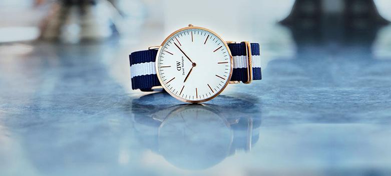 Młodzieżowy, męski zegarek Daniel Wellington 0552DW Glasgow na parcianym pasku w kolorze niebiesko białym oraz skórzanym. Okrągła koperta zegarka jest wykonana ze stali w kolorze różowego złota. Analogowa tarcza zegarka jest w minimalistycznym stylu, w białym kolorze z indeksami oraz wskazówkami w kolorze różowego złota.