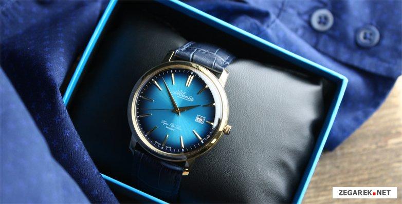 Elegancki, męski zegarek Atlantic 64351.45.51 Super De Luxe na skórzanym niebieskim pasku z stalową koperta pokrytą złotym PVD. Analogowa tarcza zegarka Atlantic jest w niebieskim kolorze z datowniekiem na godzinie 3. Indeksy oraz wskazówki są w tylko samym kolorze złota co koperta zegarka.