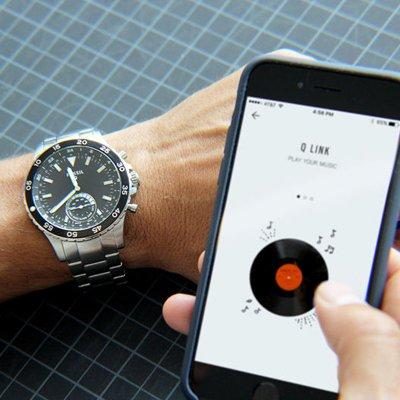 Amerykański, męski zegarek Fossil FTW1126 Q Crewmaster Hybrid Smartwatch na srebrnej, klasycznej bransolecie ze stali. Koperta zegarka Fossil jest z stali w srebrnym kolorze, koperta zegarka jest w czarnym kolorze z subtarczą oraz indeksami w białym kolorze.