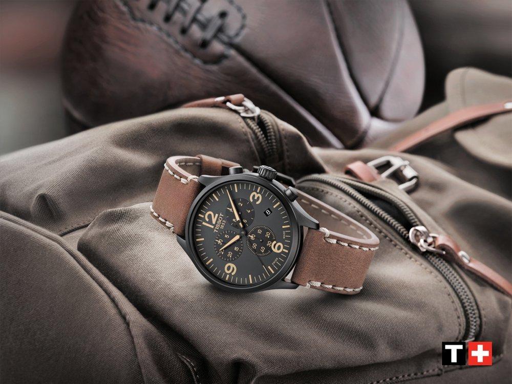 Klasyczny, męski zegarek Tissot T116.617.36.097.00 CHRONO XL na skórzanym brązowym pasku oraz stalową, okrągłą kopertą w srebrnym kolorze. Analogowa tarcz zegarka jest w kolorze zielonym z subtarczami oraz datownikiem pokazującym dzień tygodnia. Wszystkie indeksy, wskazówki oraz oznakowania na tarczy są w kolorze beżowym.