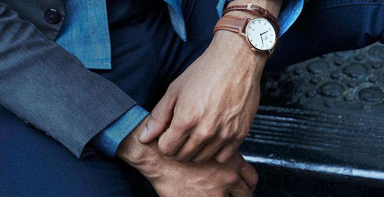 Modny, męski zegarek Daniel Wellington DW00100109 Durham na skórzanym pasku w brązowym kolorze. Koperta zegarka została zrobiona ze stali w kolorze różowego złota. Analogowa tarcza zegarka jest w białym kolorze z czarnymi wskazówkami.