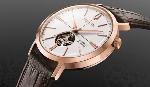 Klasyczny, męski zegarek Bulova na skórzanym pasku w brązowym kolorze z stalową, okrągłą kopertą w kolorze różowego złota. Analogowa tarcza zegarka Bulova jest w białym kolorze w stylu open heart pokazując kawałek mechanizmu zegarka. Wskazówki zegarka jak i indeksy są minimalistyczne w kolorze różowego złota.