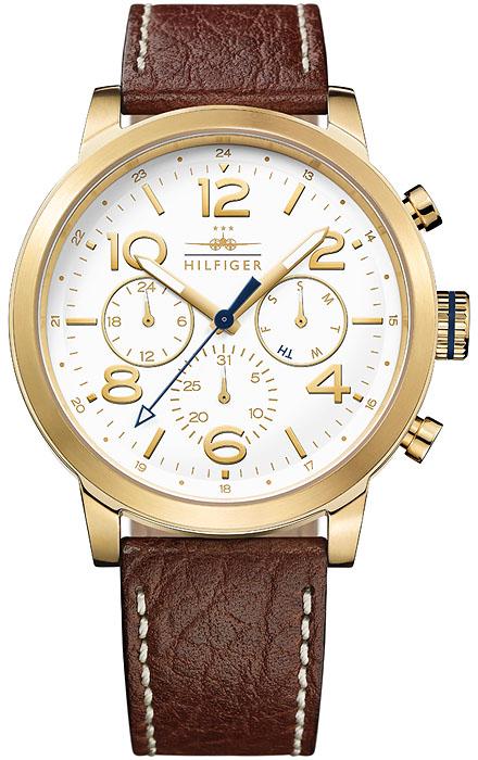 Amerykański, męski zegarek Tommy Hilfiger 1791231 na skórzanym pasku w brązowym kolorze z jasnymi szwami po bokach w beżowym kolorze. Koperta zegarka Tommy Hilfiger jest okrągła ze stali pokrytą powłoką PVD. Tarcza zegarka jest w białym kolorze z złotymi indeksami jak i subtarczami. Wskazówka sekundnika zegarka Tommy Hilfiger jako jedyna jest w czarnym kolorze.