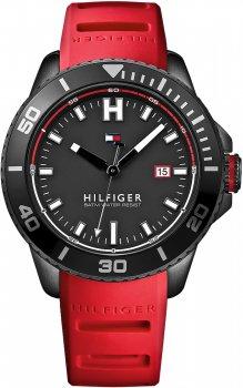 Sportowy, męski zegarek Tommy Hilfiger 1791264 na pasku z tworzywa sztucznego w czerwonym kolorze z okrągłą, stalową kopertą w czarnym kolorze. Analogowa tarcza jest w czarnym kolorze z datownikiem na godzinie trzeciej. Indeksy zegarka są w białym kolorze, a wskazówki w czarnym.