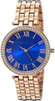 Biżuteryjny, damski zegarek Anne Klein AK-2230CBRG na bransolecie wykonanej z metalu w kolorze różowego złota. Okrągła koperta zegarka jest z metalu w kolorze różowego złota z cyrkoniami. Tarcza zegarka jest niebieska z indeksami wskazówkami w kolorze różowego złota.