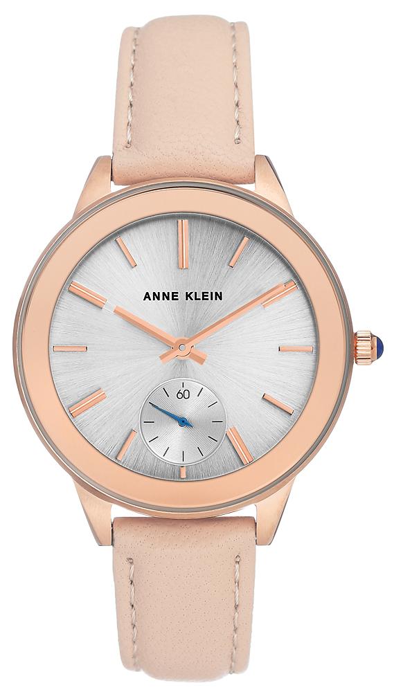 Amerykański, damski zegarek Anne Klein AK-2980RGLP na skórzanym pasku w delikatnym różowym odcieniu z różową kopertą zrobioną ze stali. Analogowa tarcza jest w srebrnym kolorze z różowymi indeksami oraz sekundnikiem w srebrnym kolorze z niebieską wskazówką.