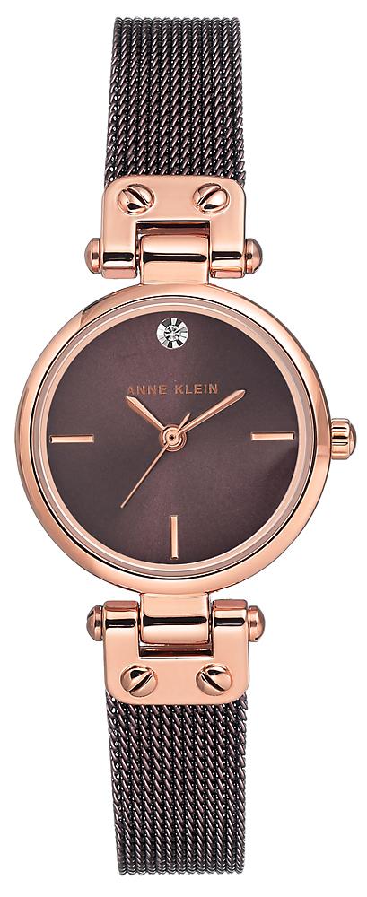Elegancki, damski zegarek Anne Klein AK-3003RGBN na stalowej bransolecie w kolorze różowego złota, stalowa koperta jest w okrągłym kształcie w kolorze różowego złota. Analogowa tarcza jest utrzymana w minimalistycznym klimacie z indeksami w kolorze różowego złota. Na godzinie dwunastej znajduje się diamencik dodający elegancji zegarkowi Anne Klein.