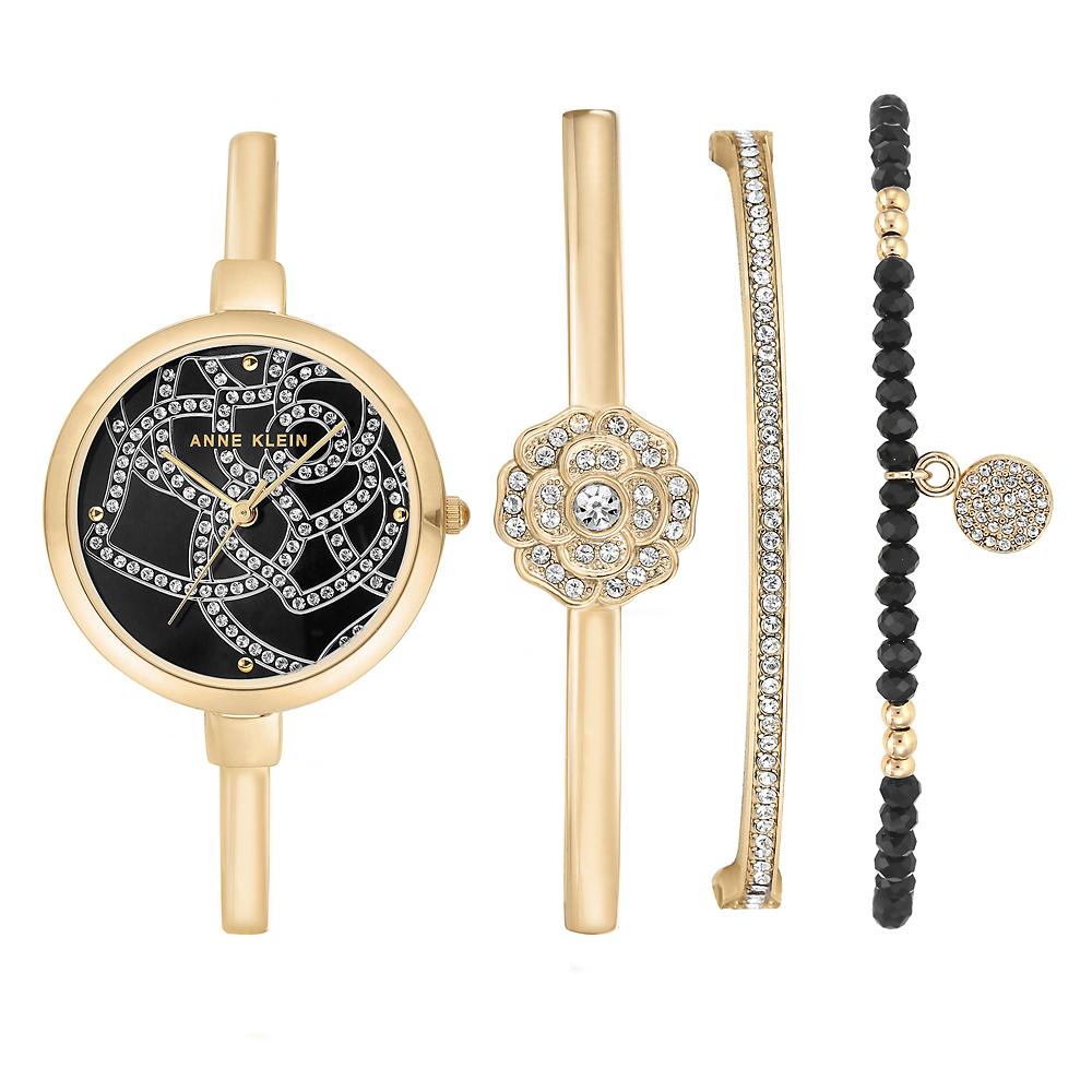 Biżuteryjny, damski zegarek Anne Klein AK-3080GBST na stalowej złotej bransolecie i kopercie. Analogowa tarcza zegarka jest w czarnym kolorze z wygrawerowanym kwiatkiem róży ozdobionym cyrkoniami.