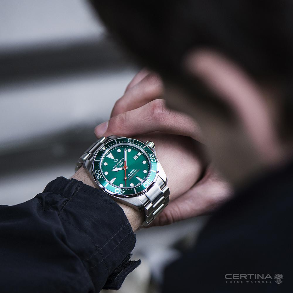 Klasyczny, męski zegarek Certina na stalowej bransolecie oraz koperta w srebrnym i zielonym kolorze ze stali. Tracza zegarka jest w zielonym kolorze z białym datownikiem oraz indeksami. Na tle zielonej tarczy wyróżnia się czerwona wskazówka sekundnika.