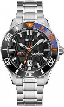Luksusowy, męski zegarek Doxa D200SBU Shark Ceramica na bransolecie oraz z kopertą wykonaną ze stali w srebrnym kolorze. Bezel zegarka jest wykonany z porcelany w kolorach takich jak czarny, niebieski oraz pomarańczowy. Giloszowana tarcza zegarka została wykonana z ceramiki. Na analogowej tarczy koło godziny czwartej znajduję się rekin oraz na godzinie szóstej jest datownik pokazujący dzień miesiąca. Wskazówki jak i indeksy są w srebrnym kolorze oprócz wskazówki sekundnika, która jest w pomarańczowym kolorze.