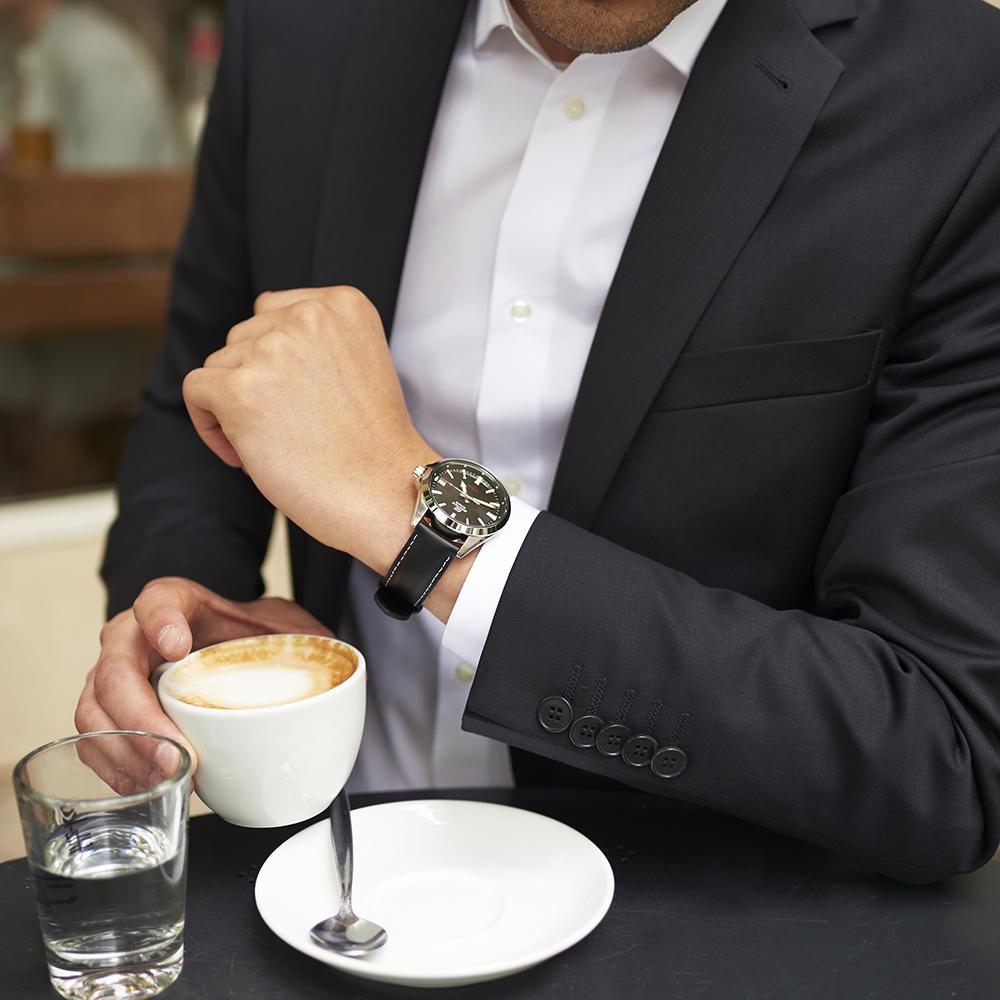 Klasyczny, kwarcowy zegarek męski na czarnym skórzanym pasku oraz czarna analogowa tarczą ze srebrną kopertą.