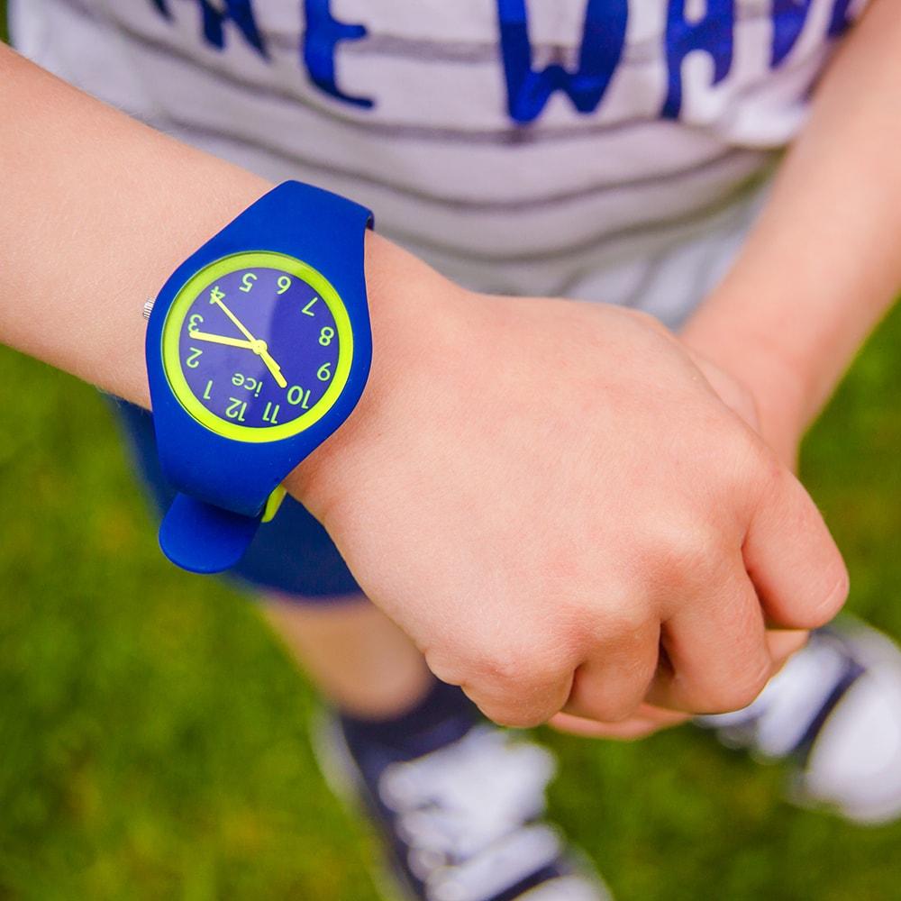 Dziecięcy zegarek Ice Watch ICE.014427 ICE ola kids rocket na silikonowym pasku w niebieskim kolorze oraz kopercie wykonanej z tworzywa sztucznego w takim samym kolorze jak pasek. Analogowa tarcza zegarka jest w tym samym odcieniu co pasek a indeksy, wskazówki i bezel są w kolorze zielonym.
