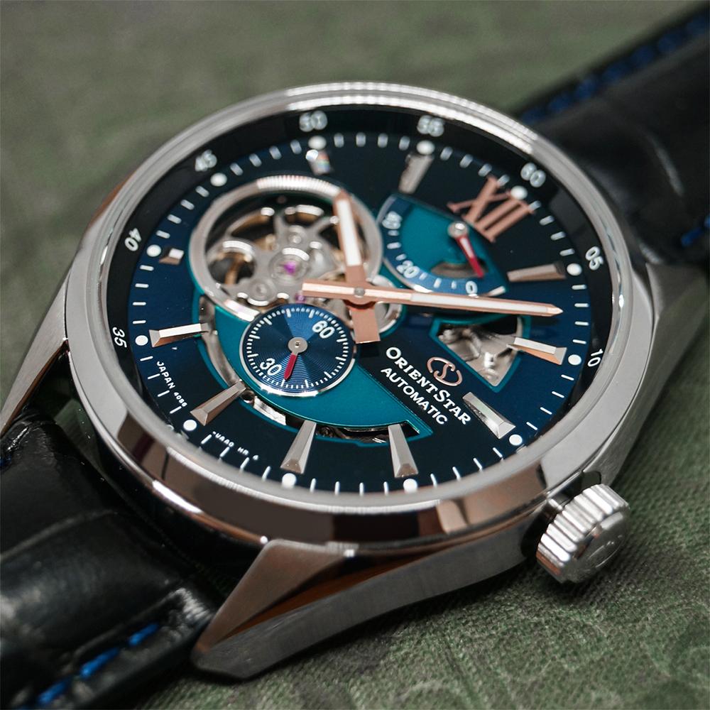Zegarel Orient Star z mechanizmem automatycznym, z srebrną kopertą oraz ciemno niebiseką kopertą z wycięciem w tarczy przedstawiającym mechanizm.