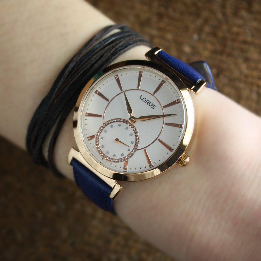 Klasyczny, damski zegarek Lorus RN418AX7 Fashion na skórzanym niebieskim pasku z kopertą zrobioną z mosiądzu, tarcza jest biała z indeksami w kolorze różowego złota oraz została przyozdobiona kryształkami.
