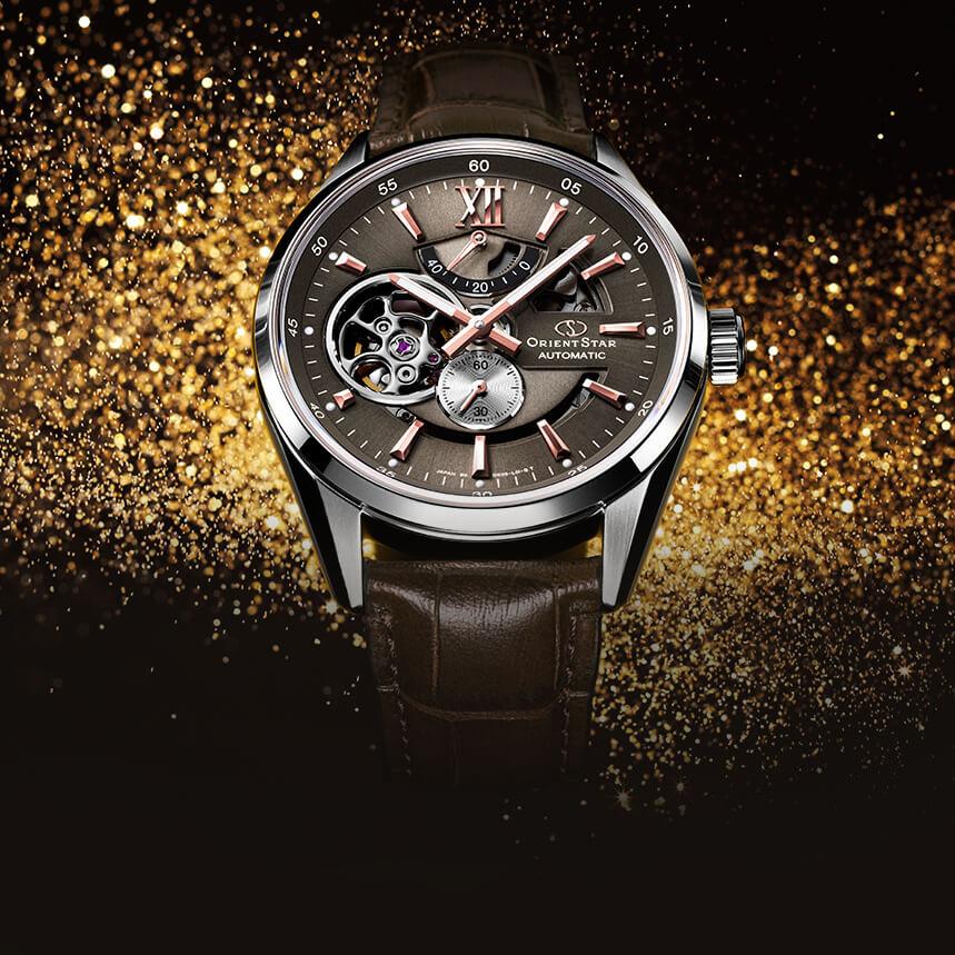 Zegarek Orient Star z mechanizmem automatycznym na brązowym skórzanym pasku, srebrną kopertą oraz dekoracją open heart na tarczy.