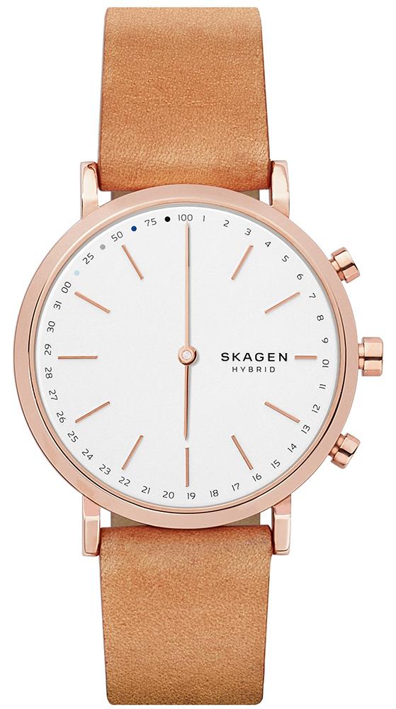 Klasyczny, męski smartwatch Skagen SKT1204 Hald na skórzanym brązowym pasku z stalowa koperta w kolorze różowego złota. Analogowa tarcza w białym kolorze z brązowymi indeksami jak i wskazówkami oraz małymi cyferkami i logo w czarnym kolorze.