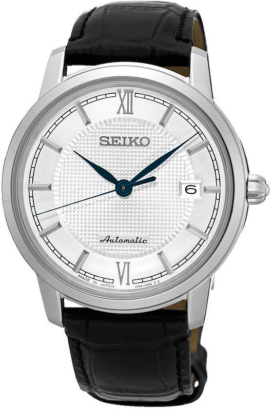 Luksusowy, męski zegarek Seiko Presage SRPA13J1 na skórzanym pasku w czarnym kolorze oraz okrągłej stalowej tarczy w srebrnym kolorze.Zegarek ma mechanizm automatyczny a jego analogowa tarcza jest w białym kolorze z datowniekiem oraz skromnymi wskazówkami w atramentowym odcieniu.