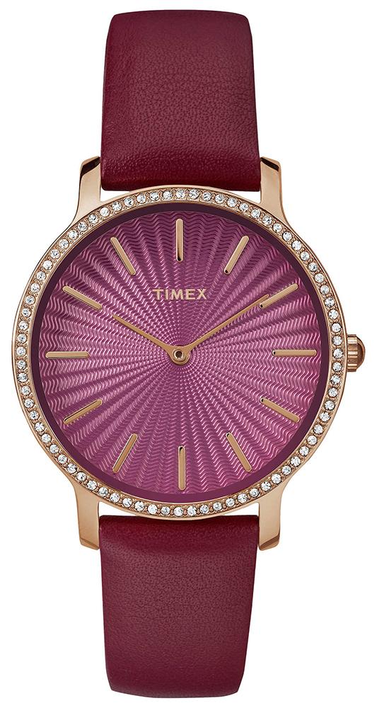Kobiecy zegarek Timex w różowym kolorze. Zegarek posiada stalowa tarczę w kolorze różowego złota ozdobioną cyrkoniami. Sama tarcza tego modelu jest zrobiona z techniką gliszowania.