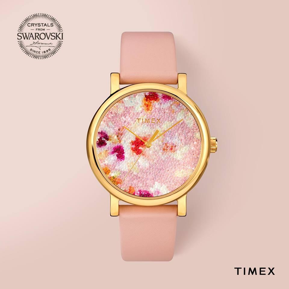 Klasyczny zegarek Timex TW2R66300 z wielokolorową tarczą ozdobioną diamencikami Swarovskiego. Zegarek Timex jest na różowym pasku z złotą kopertą.