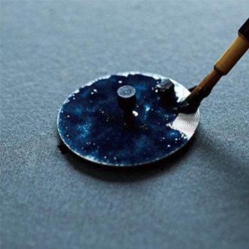Granatowa, emaliowana tarcza przypominająca wyspiarski charakter Japonii.