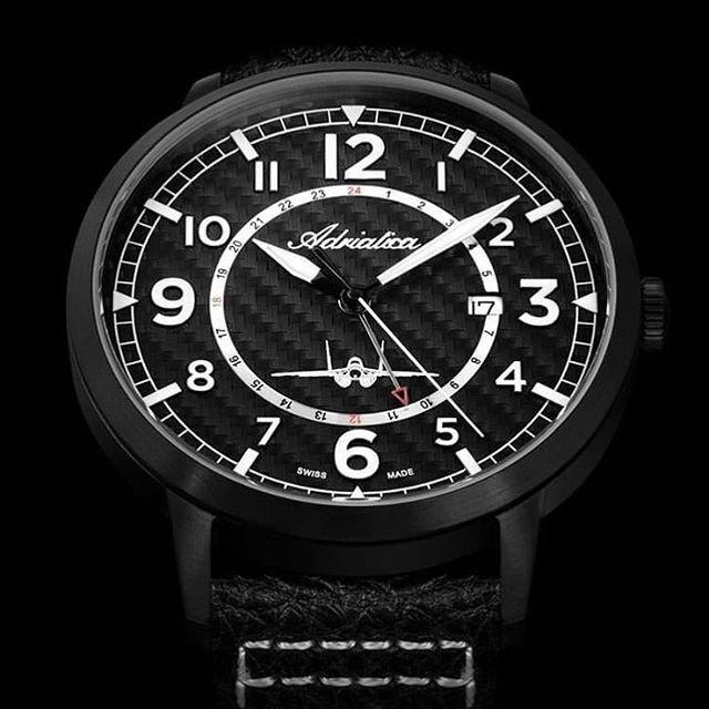Czarny, meski zegarek Adriatica Aviation z białymi indeksami na tarczy oraz samolotem.
