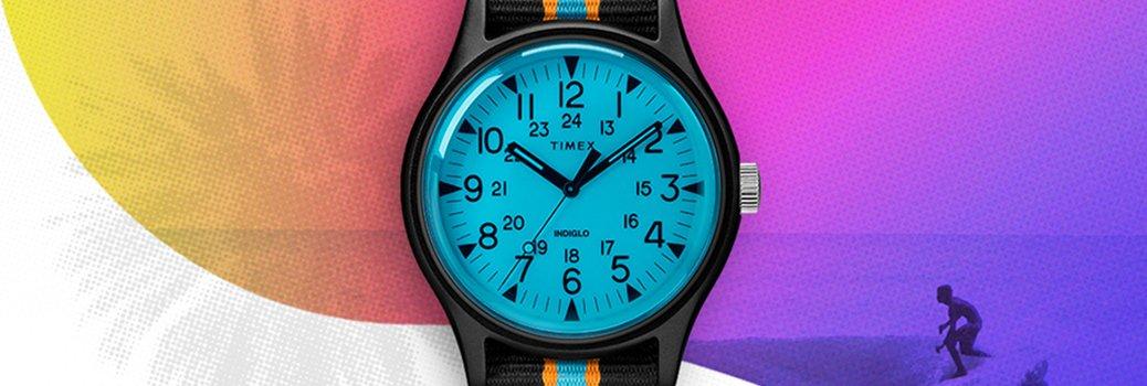 Młodzieżowy zegarek Timex TW2T25400 Aluminum California z mechanizmem kwarcowym. Zegarek jest z aluminiową kopertą w czarnym kolorze i parcianym pasku w czarnym, pomarańczowym oraz niebieskim kolorze.