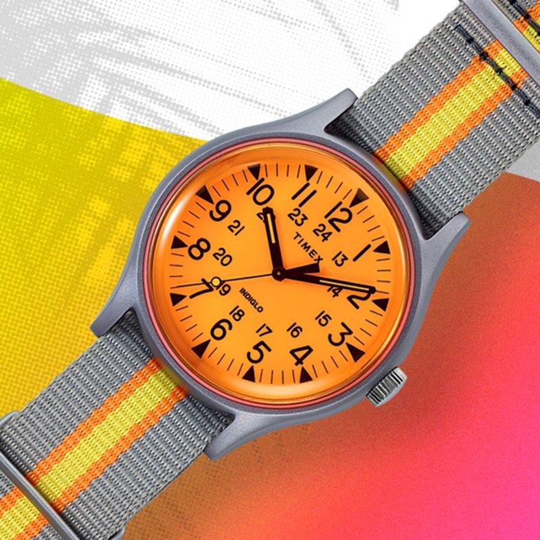 Młodzieżowy zegarek Timex TW2T25500 Aluminum California z mechanizmem kwarcowym. Zegarek jest z aluminiową kopertą w srebnrym kolorze i parcianym pasku w szarym, pomarańczowym i żółtym kolorze.
