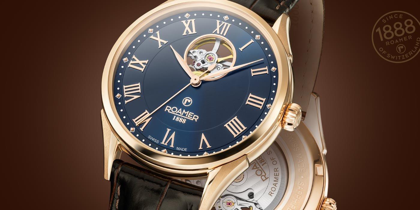 Klasyczny zegarek Roamer na skórzanym brązowym pasku z złotą kopertą oraz niebieską tarczą.
