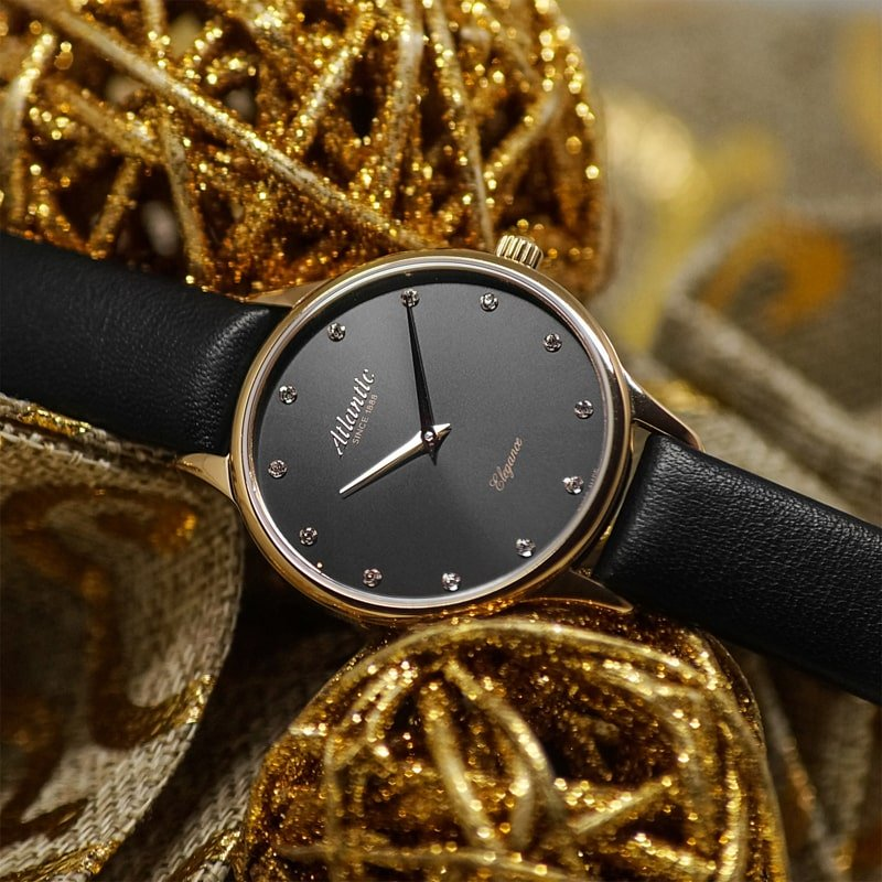Szwajcarski, damski zegarek Atlantic z analogową tarczą w czarnym kolorze ozdobiona cyrkoniami w miejscu indeksów. Koperta zegarka jest w kolorze różowego złota na czarnym skórzanym pasku.