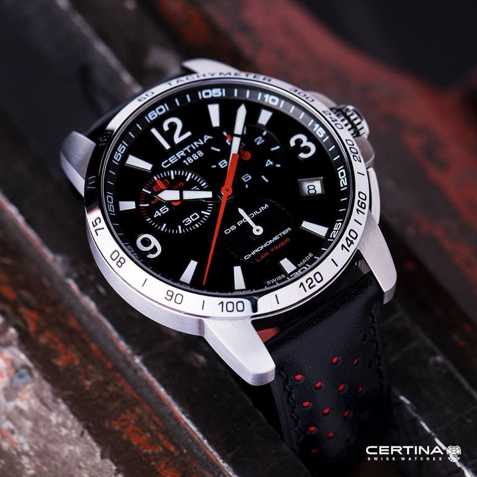 Luksusowy, męski zegarek Certina C034.453.16.057.00 DS Podium Chronograph Lap Timer na czarnym skórzanym pasku z czerwonymi akcentami, okrągła koperta wykonana ze stali w srebrnym kolorze. Analogowa tarcza zegarka jest w czarnym kolorze z białymi indeksami oraz wskazówkami jak i z detalami w czerwonym kolorze.