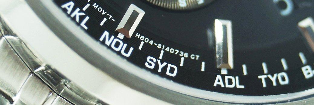 Zegrek z srebrną branzoletą i czarną tarczą na której jest umożliwiony jest odczyt godziny w róznych strefach czasowych.