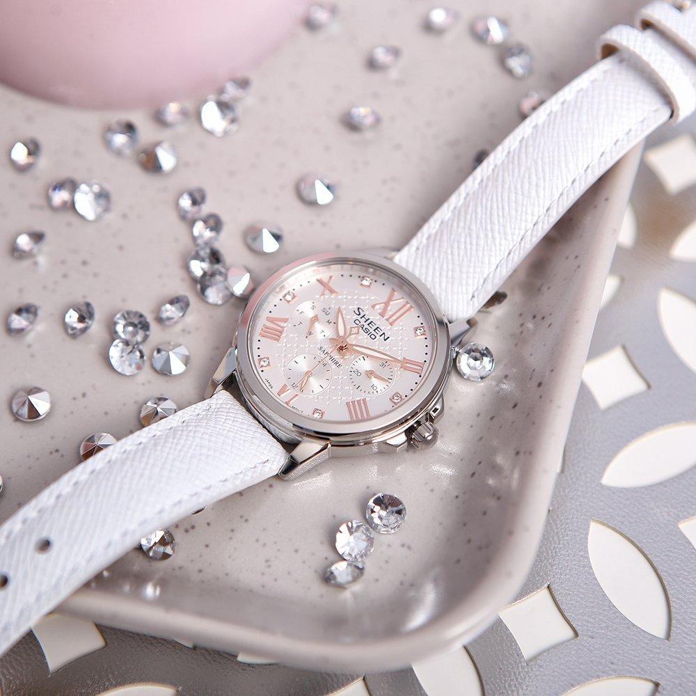 Piękny, damski zegarek Casio Sheen na białym pasku z stalową okrągłą kopertą oraz giloszowaną tarczą w srebrnym kolorze z trzema subtarczami. Wskazówki jak i indeksy są w kolorze różowego złota a tarcza ozdobiona jest kryształkami Swarovskiego.