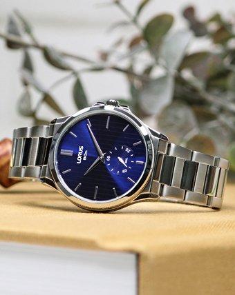 Klasyczny zegarek Lorus na ciemno niebieskiej analogowej tarczy w prążki z srebrną bransoletą.