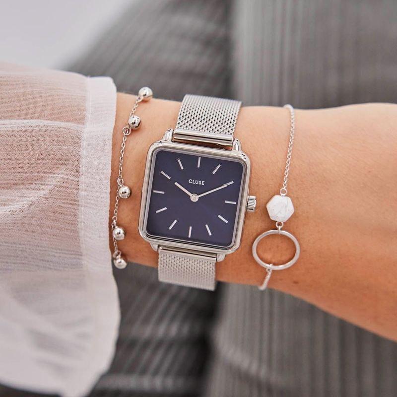 Minimalistyczny zegarek Cluse na srebrnej bransolecie mesh z ciemną tarczą w kwadratowym kształcie.