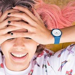 Zegarek Swatch dla dzieci na niebieskim pasku z niebieską kopertą. Tarcza zegarka jest biała z ciemnymi wskazówkami.