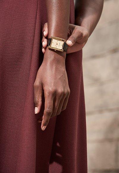 Kobiecy, damski zegarek Anne Klein na skórzanym pasku w brązowym kolorze z złota koperta wykonana ze stali. Analogowa tarcza zegarka jest w beżowym kolorze z złotymi wskazówkami oraz indeksami.
