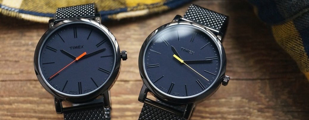 Klasyczne, męskie zegarki Timex na czarnej bransolecie typu mesh z czarną koperta oraz tarczą. Wskazówki sekundników są w dwóch kolorach jedna w czerwonym, druga w żółtym.