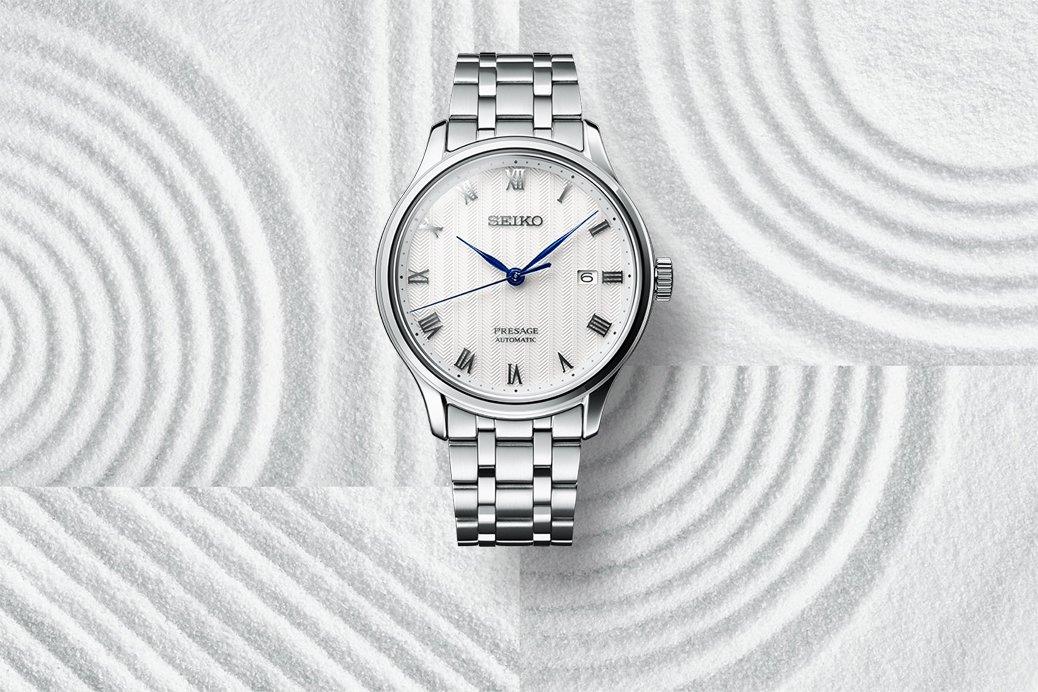 Klasyczny zegarek Seiko Presage na srebrnej bransolecie z białą tarczą oraz datownikiem.