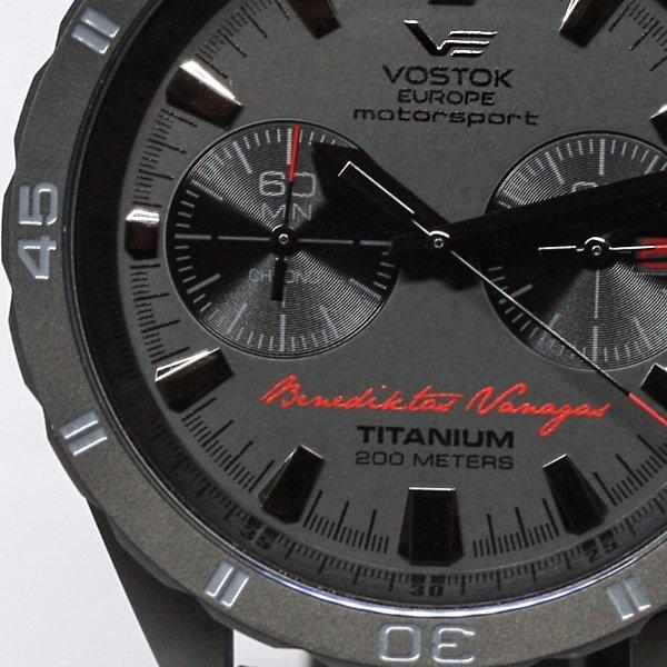 Luksusowy, męski zegarek Vostok Europe 6S21-320H391 Motorsport Benediktas Vanagas Titanium Black Edition na skórzanym pasku w kolorach takich jak czerwony i czarny. Koperta zegarka jest wykonany z tytanu w czarnym kolorze. Tarcza zegarka jest również w czarnym kolorze z dwiema subtarczami. Na dole tarczy widnieje napis Benediktas Vanagas w czerwonym kolorze.