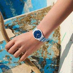 Zegarek dla dzieci Swatch na pasku w paski z białą kopertą oraz granatową tarczą.