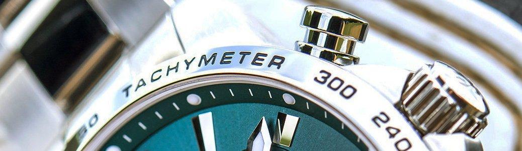 Zegarek tachymetr z srebrnym bezelem oraz morską tarczą, umożliwiający pomiar prędkości w kilometrach lub milach na godzinę.