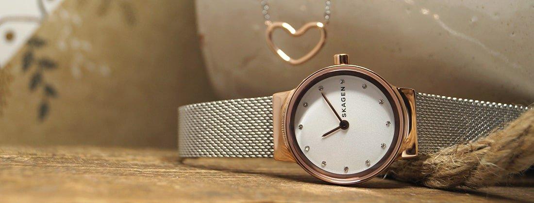Elegancki, damski zegarek Skagen SKW1101 FREJA na srebrnej bransolecie typu mesh oraz kopertą ze stali w kolorze różowego złota. Biała tarcza zegarka jest minimalistyczna ozdobiona dwunastoma kryształkami. Wskazówki są w kolorze różowego złota w postaci kresek.