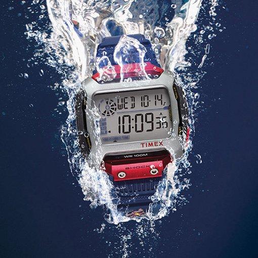 Wstrząsoodporny zegarek Timex na ciemno niebieskiej bransolecie z czerwonymi akcentami przy kopercie.