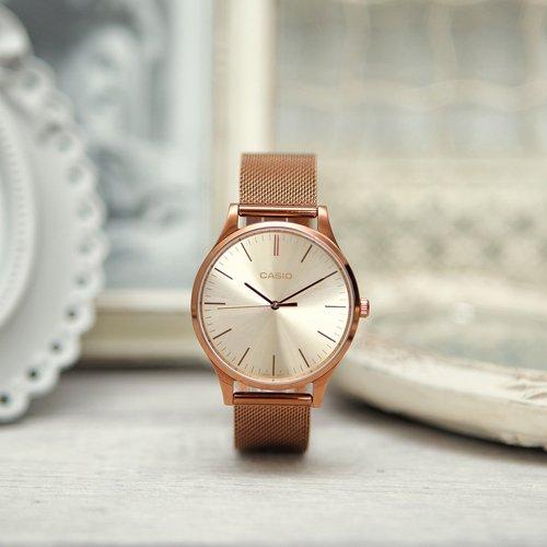 Damski zegarek Casio Instashape LTP-E140R-9AEF na różowo złotej bransolecie typu mesh z klasyczną złotą tarczą.