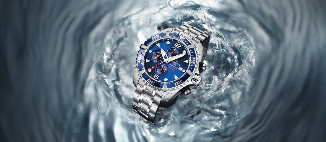 Wodoodporny zegarek Certina na srebrnej bransolcie z niebieskim bezelem i niebieską tarczą.