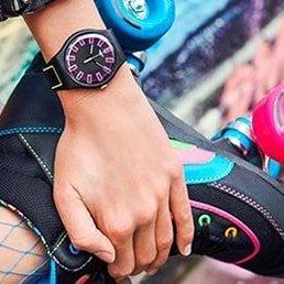 Dziecięcy zegarek Swatch na czarnym pasku z zieloną pręgą. Koperta zegarka jest czarna jak i tarcza, na tarczy można również zobaczyć różowe prostokąty.