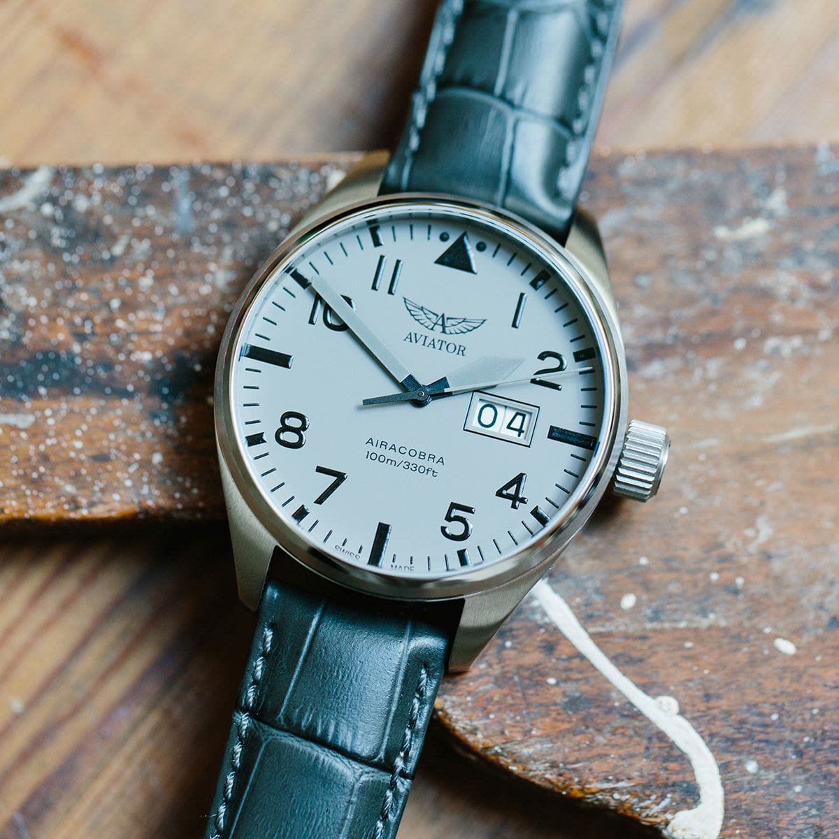 Elegancki, męski zegarek Aviator na skórzanym niebieskim pasku z srebrną stalową kopertą. Analogowa tarcza zegarka jest w kolorze białym z czarnymi indeksami oraz datownikiem na godzinie 3.